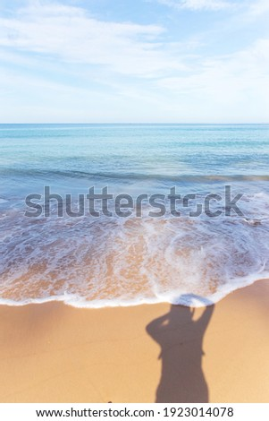 Shadow of women take a photo herself in sunny day with beautiful blue sea. Great vacation alone with sound of nature.