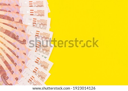Banknotes with a face value of five thousand Russian rubles on a yellow background. Top view, free space for text Royalty-Free Stock Photo #1923014126