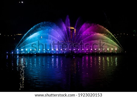 A dancing fountain, or fountain, formed by a controlled ascending and descending rainbow-like lights.  And the color reflecting on the water. Royalty-Free Stock Photo #1923020153