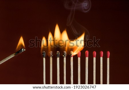 Lit match next to a row of lighting matches. Red phosphorus matches on dark red background. Concept of ignition or initiationv Royalty-Free Stock Photo #1923026747
