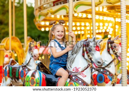 happy baby girl rides a carousel on a horse in an amusement Park in summer Royalty-Free Stock Photo #1923052370