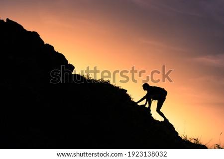 Young man climbing up mountain  Royalty-Free Stock Photo #1923138032