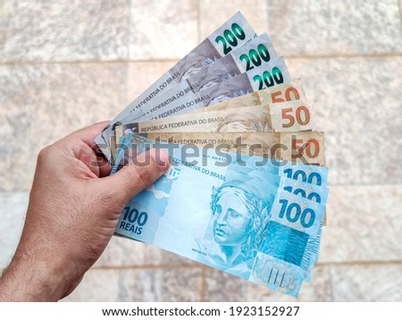 Real currency, money from Brazil. Brasil, Dinheiro, Reais, Hand. People holding in hand a brazilian banknotes. Royalty-Free Stock Photo #1923152927