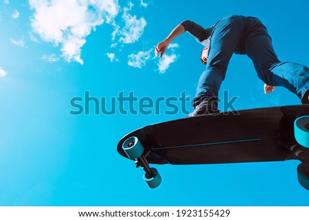 Skater in action. Man making a trick on a longboard outdoors on sunny summer day. Blue sky background. Concept of extreme sport active lifestyle Royalty-Free Stock Photo #1923155429