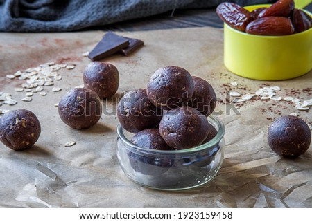Healthy energy protein balls with dates, oats, peanut butter and dark chocolate. Homemade gluten free truffle bites with no bake. Vegan and vegetarian raw appetizer or food snack. Side view Royalty-Free Stock Photo #1923159458