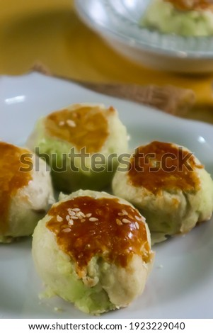 unfocus picture of Some delicious bakpia are put on white plate, bakpia is a baked flour roll filled with green beans and sugar from Indonesia served with some tea. Isolated. Top view
