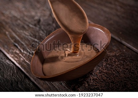 Chocolate Easter egg stuffed with chocolate sauce. Royalty-Free Stock Photo #1923237047