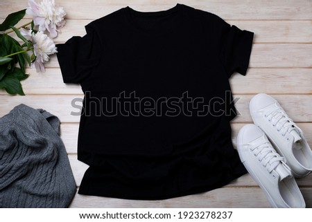 Black women's cotton T-shirt mockup with gray aran sweater, white sneakers and pale pink peony. Design t shirt template, tee print presentation mock up Royalty-Free Stock Photo #1923278237