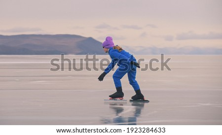 The girl train on ice speed skating. The child skates in the winter in blue sportswear suit, sport glasses. Children speed skating sport. Outdoor slow motion. Snow capped mountains, beautiful ice.