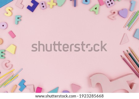 Wooden toys, letters, a horse on a pastel pink background. Trendy cute baby first toys. Eco-friendly, plastic-free set of accessories for kids. Toys for kindergarten, preschool, or daycare. Close up