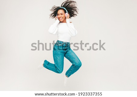 Beautiful black woman with afro curls hairstyle.Smiling model in sweater and jeans.Sexy carefree female listening music in wireless headphones. Jumping in studio on white background.Dynamic movement