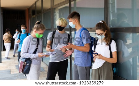 Teen students in medical face masks standing with workbooks in schoolyard during break in lessons. Concept of back to school after lockdown Royalty-Free Stock Photo #1923359279