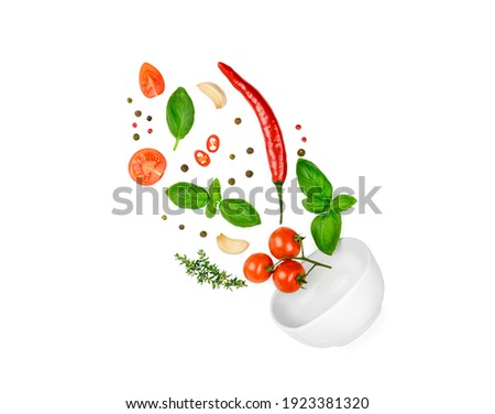 Tomato, basil, spices, chili pepper, garlic fresh thyme flying. Vegan diet food isolated on white. Falling into bowl, levitation fly. Creative concept. High quality photo Royalty-Free Stock Photo #1923381320