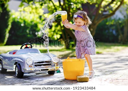 Cute gorgeous toddler girl washing big old toy car in summer garden, outdoors. Happy healthy little child cleaning car with soap and water, having fun with splashing and playing with sponge. Royalty-Free Stock Photo #1923433484