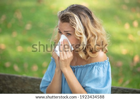 blond woman blowing nose outdoors Royalty-Free Stock Photo #1923434588
