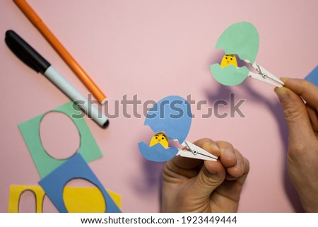 How to make funny children's paper craft. Moving Easter toys in egg shape on clothespin.Step by step instructions. Easy paper applications in kindergarten or at home. DIY concept. Step 8.Final result Royalty-Free Stock Photo #1923449444