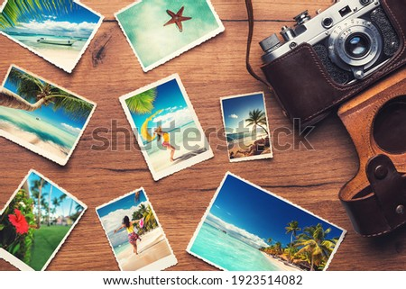 Vintage retro camera with tropical beach photos on wooden background