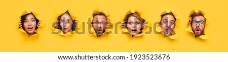 Collage of curious shocked young people peeking out of torn holes in yellow paper and looking at camera Royalty-Free Stock Photo #1923523676