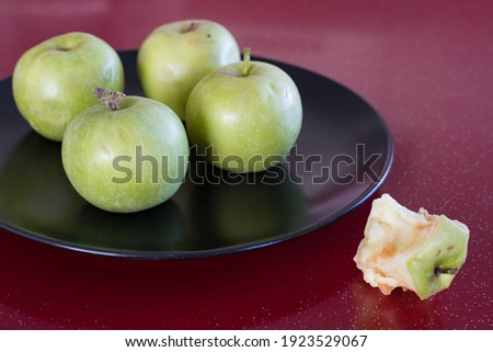 A few green fresh apples and a stub of a eaten apple lie on a black platter on a red table, There is a free space for the inscription.