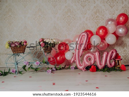 San Valentin mini photoshoot for babies and toddlers in a photo studio with a bicycle full of flowers and balloons