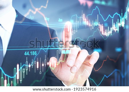 Stock market trading concept with businessman touching digital screen with glowimg financial graphs and diagram. Double exposure Royalty-Free Stock Photo #1923574916