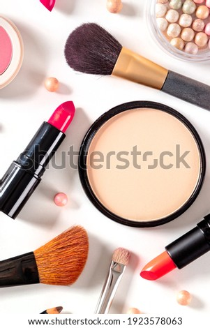Makeup products and tools, shot from above on a white background. Lipstick, brushes, pearls, etc