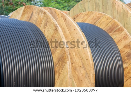Wooden Coils Of Electric Cable Outdoor. High and low voltage cables in the storage. Royalty-Free Stock Photo #1923583997