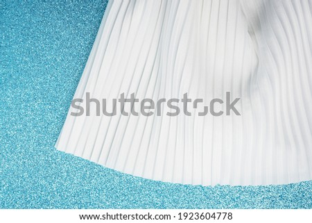 Top view of milky coloured skirt. High quality white silk pleated material. Natural fiber. Tailoring and fashion industry concept. Fabric clothing on blue glitter backdrop, copy space
