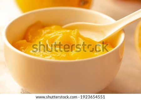 Homemade fresh pudding or tangy lemon curd in a white bowl.Selective focus. Royalty-Free Stock Photo #1923654551