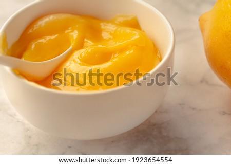 Composition with delicious Yellow lemons and Lemon curd in a sausepan white bowl on marble background. Royalty-Free Stock Photo #1923654554
