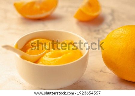 Composition with delicious Yellow lemons and Lemon curd in a sausepan white bowl on marble background. Royalty-Free Stock Photo #1923654557