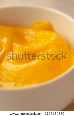 Composition with delicious Yellow lemons and Lemon curd in a sausepan white bowl.Close-up. Royalty-Free Stock Photo #1923654560