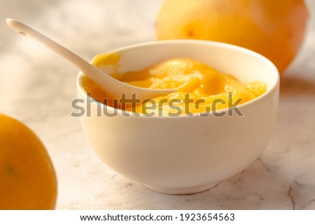Composition with delicious Yellow lemons and Lemon curd in a sausepan white bowl on marble background. Royalty-Free Stock Photo #1923654563