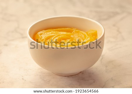 Homemade fresh pudding or tangy lemon curd in a white bowl on marble background. Royalty-Free Stock Photo #1923654566
