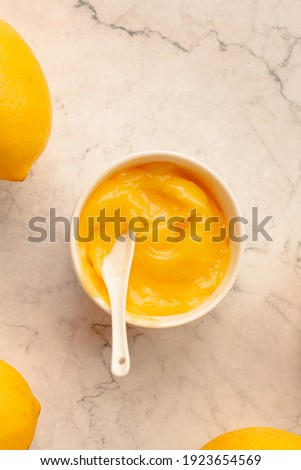 Delicious homemade tangy lemon curd decorated with fresh fruit on marble background.Top view. Royalty-Free Stock Photo #1923654569
