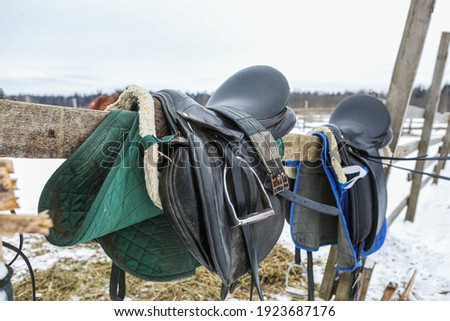 Picture of vintage horse leather saddle. Horse stables in the background, as well as natural winter forest reserve.