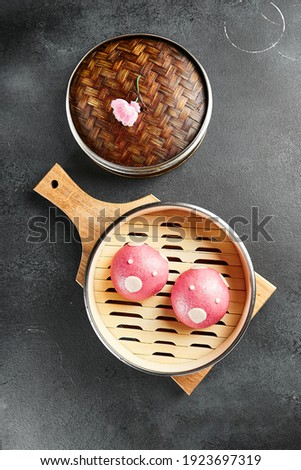 Closed bao bun with sweet berry inside. Delicious chinese steamed sweet food. Chinese, asian, authentic food concept. Royalty-Free Stock Photo #1923697319