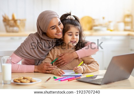Happy Muslim Mom In Hijab And Her Little Daughter Using Laptop In Kitchen, Having Fun Together At Home, Watching Cartoons Or Kids Development Videos Online, Small Girl Is Drawing At Table, Free Space