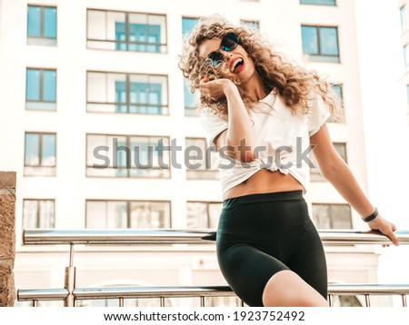 Portrait of beautiful smiling model with afro curls hairstyle dressed in summer hipster clothes.Sexy carefree model posing in the street background. Trendy funny and positive woman having fun