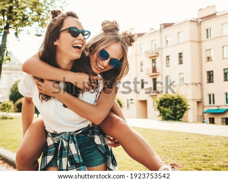 Two young beautiful smiling hipster female in trendy summer white t-shirt clothes.Sexy carefree women posing on street background. Model jumping on her friend back, gives piggyback riding outdoors