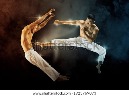 Two martial arts masters, karate practice. On black background Royalty-Free Stock Photo #1923769073