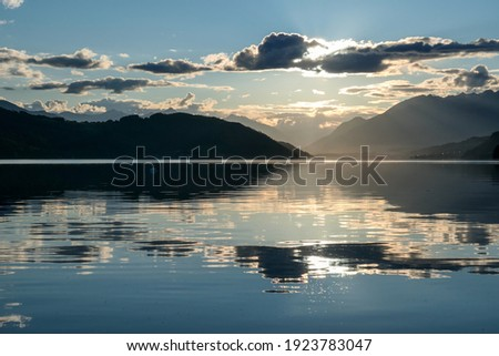 A sunset by Millstaetter lake in Austria. The lake is surrounded by high Alps. Calm surface of the lake reflecting the sunbeams. The sun sets behind the mountains. A bit of overcast. Natural beauty Royalty-Free Stock Photo #1923783047