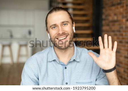 Young European man looking at the camera, smiling and waving the hand, positive person with bewitching smile, say hi, with white earphones, greeting family or friends by video, wearing blue shirt Royalty-Free Stock Photo #1923795200