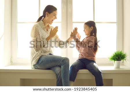 Happy family having fun at home. Mom and little child spending time together. Young mother and cute daughter playing patty cake sitting on windowsill of plastic window back lit with bright sunlight Royalty-Free Stock Photo #1923845405