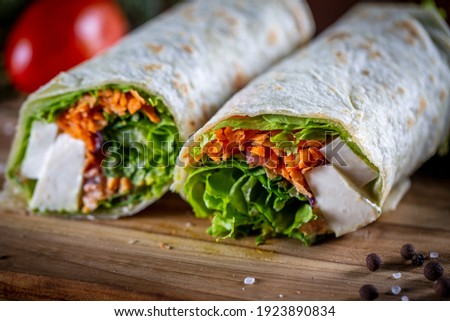 Vegetarian wrap sandwich on wooden background Royalty-Free Stock Photo #1923890834