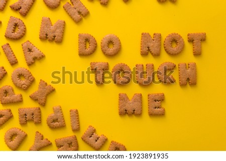 Word Do Not Touch Me in the middle of the picture made of tasty crunchy cookies in form of English alphabet letters, textured bright yellow background, health, dieting and medical concept. Copy space