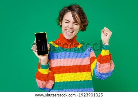 Joyful young brunette woman 20s years old wearing casual colorful sweater hold mobile cell phone with blank empty screen doing winner gesture isolated on bright green color background studio portrait