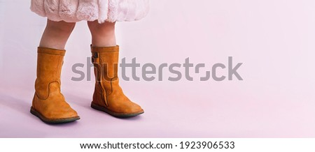 children boots shoes for little fashionistas on a pink background copyspace for text. Selective focus Royalty-Free Stock Photo #1923906533