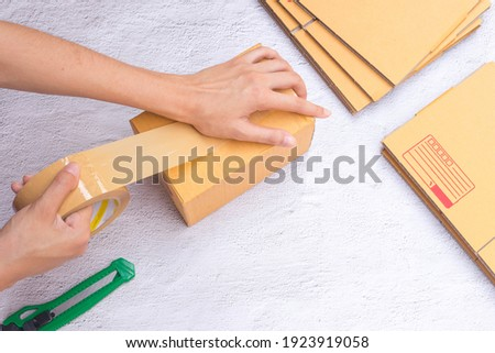 The hand of the female business owner is packing the goods for delivery Seller packs a box from e-commerce orders Postage, dropshipping shipment service concept. Royalty-Free Stock Photo #1923919058