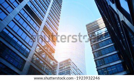 Bottom view of modern skyscrapers in business district against blue sky. Looking up at business buildings in downtown. Rising sun on the horizon. Royalty-Free Stock Photo #1923932246